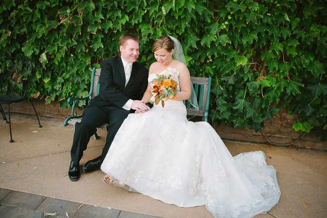 Bride and groom sitting together in front of an ivy colored wall at Viansa Winery in Sonoma County