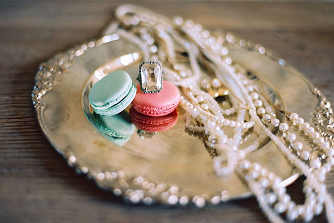 wedding bridal pearl necklace with french macarons and large cocktail ring atop a silver tray at Sunstone Villa wedding in Santa Ynez